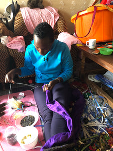 Wear the epitome of Kenya style with The Bintiah necklace.  This necklace is handmade using colorful seed beads that are intricately and tightly wrapped around a solid piece fo make a stunning statement with any outfit.   Black with colorful bead accent.  Bintiah pictured making a product.
