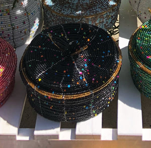 Fair Trade hand crafted basket made from seed beads. Round shape with lid. These baskets take 1 full day to create.  Black with multi color bead accent and gold bead around edge of lid.