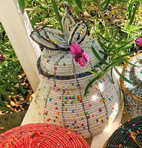 Fair Trade hand crafted basket made from seed beads in the shape of a jar with lid. Regular size baskets take at least a day to create.  Large baskets take 1 1/2 - 2 days to create. white color with multi color bead accent