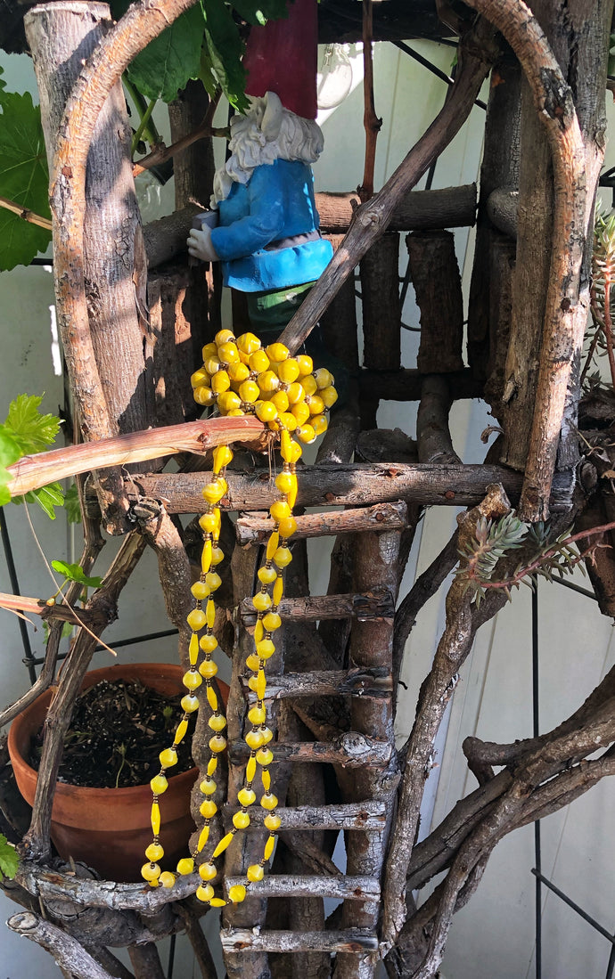 "Long handmade paper bead necklace and stretch bracelet set weathered yellow color. Necklace is approximately 30"" long and usually worn doubled. Bracelet is a stretch bracelet. Handcrafted from magazines. Fair trade.   Color Yellow stretch bracelet and necklace pictured"
