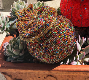 Fair Trade hand crafted basket made from seed beads in the shape of a jar with lid. Regular size baskets take at least a day to create.  Large baskets take 1 1/2 - 2 days to create. Gold multi color