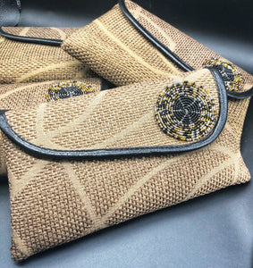 light brown clutches leaning on each other. giraffe style lines and round bead on flap