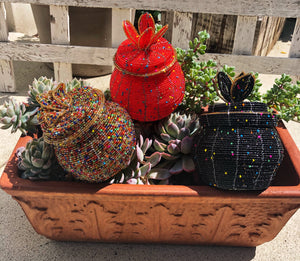 Fair Trade hand crafted basket made from seed beads in the shape of a jar with lid. Regular size baskets take at least a day to create.  Large baskets take 1 1/2 - 2 days to create. Red, Black and Gold Multi colors