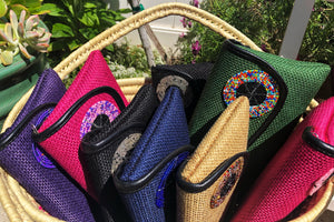 Basket of clutch purses in purple, dark pink. black, blue, tan, green, dark pink.  All have round beaded embellishment on the flap