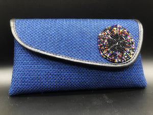blue clutch with round beads on flap and black piping around edge