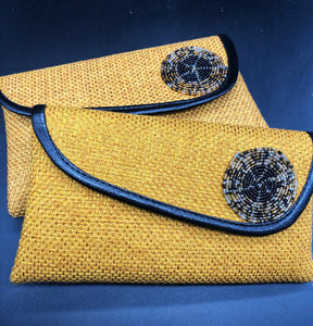 2 gold clutches, round beads on flap, black piping around flap edge
