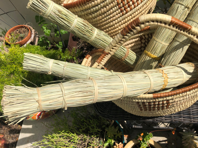 several papyrus reed brooms in a large handle basket in the garden