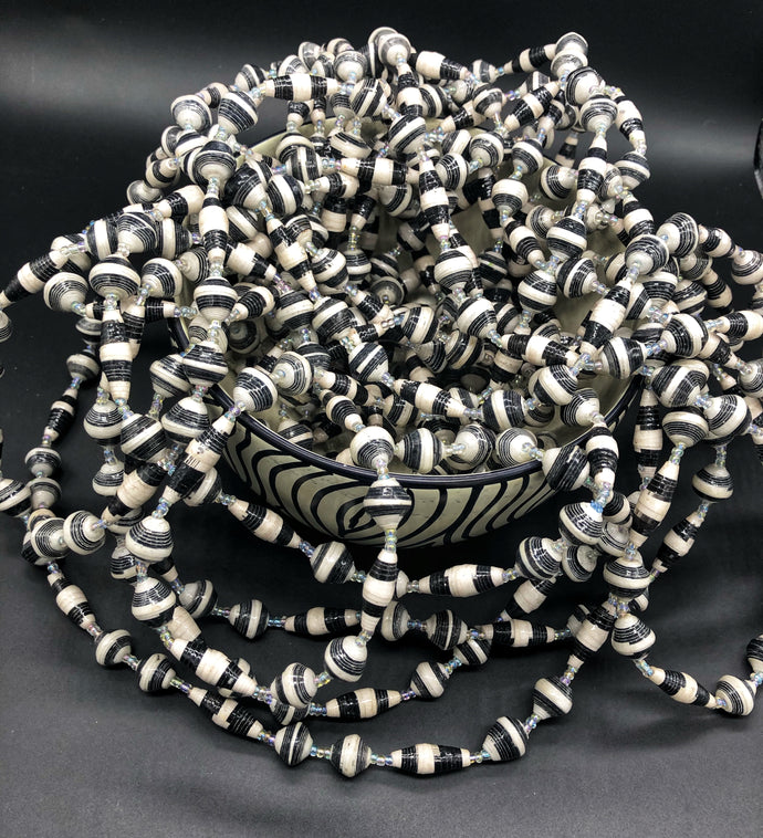 "Hand crafted black and white paper bead necklace approximately 30"" long with clear bead embellishment. Usually worn doubled. Each bead individually rolled by hand from magazines.  Stylish and Fashionable for casual or dressy. Fair trade."