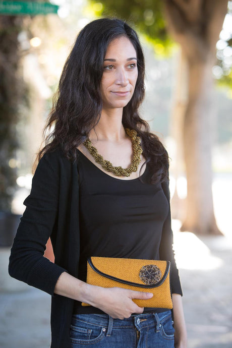 Young lady pictured from the hips up with black shirt, gold necklace and gold mini clutch purse and tree faded on the background