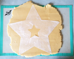 Star template made from parchment paper on cookie dough