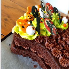 Image of chocolate cake cut into cauldon shape and decorated for Halloween