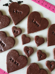 Chocolate cookies with stamped messages on them ready for baking