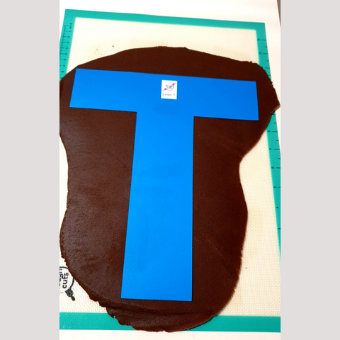Image of letter T baking stencil on rolled out chocolate cookie dough