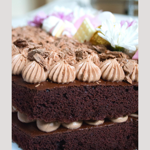 Side view of chocolate cake showing the chocolate cheesecake filling and piping on top of cake