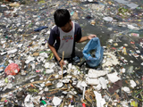 Boy standing in trash-filled water