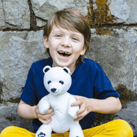 Little Boy Holding Stuffed Polar Bear Made from Recycled Plastic