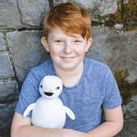 Smiling Boy Holding Stuffed Baby Beluga made from Recycled Plastic Bottles