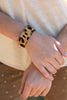 The Cuff Bracelet in Animal Print. The bracelet is an adjustable cuff bracelet with faux animal print.