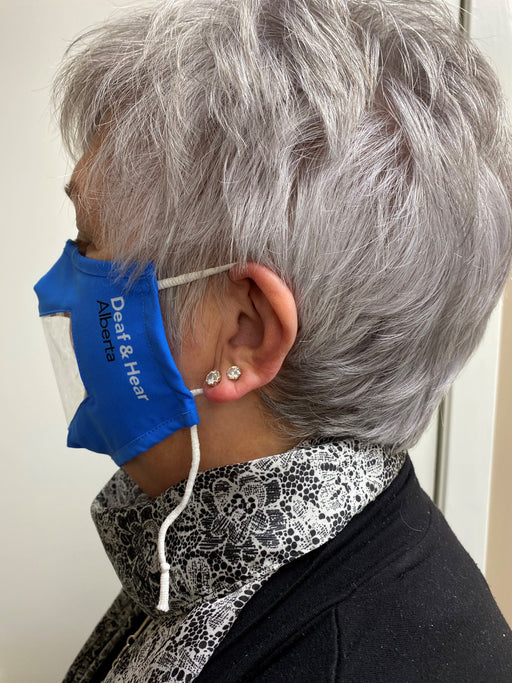 A side view of a woman wearing the Blue Fabric Mask with Clear Window and Drawstring Ear Loops Mask