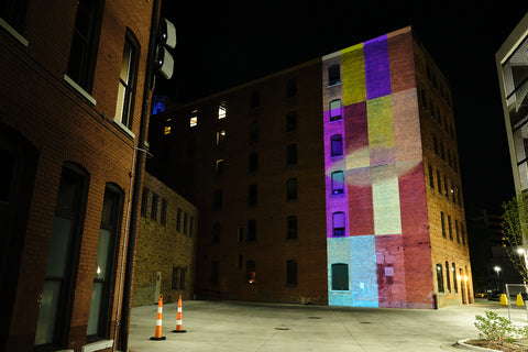 Digital Mural. Projection of colored shapes on brick building