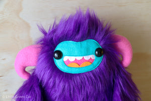 furry purple sloth monster toy with big smiling teal face and pink horns