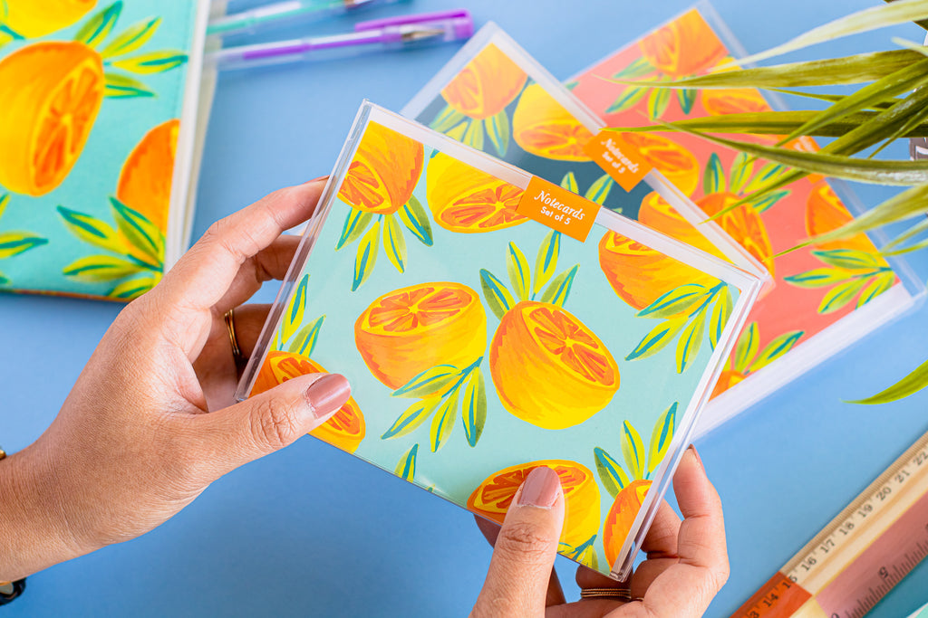 Citrus and orange stationery, eco-friendly, made from 100% post-consumer waste, pictured on a blue background