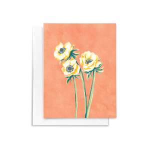 A folded note card with a hand drawn white Anemone floral bouquet illustration with white, yellow, blue, and green details on a textured peach background.