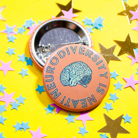 Neurodiversity is Neat Pin by Curated Dry Goods for Mental Health Association of Central Florida, pictured on a yellow background
