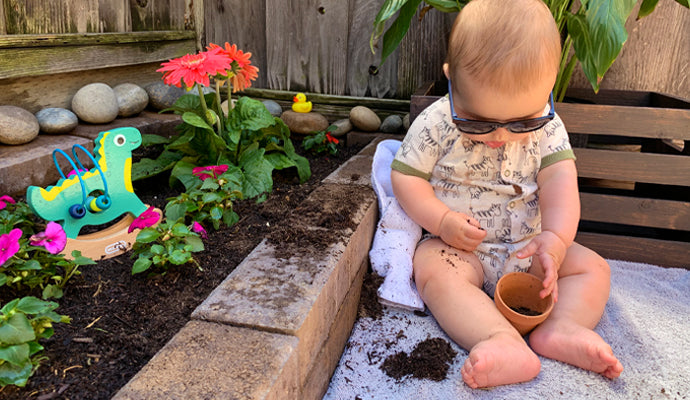Chubby baby in little sunglasses, playing with a pot in a garden