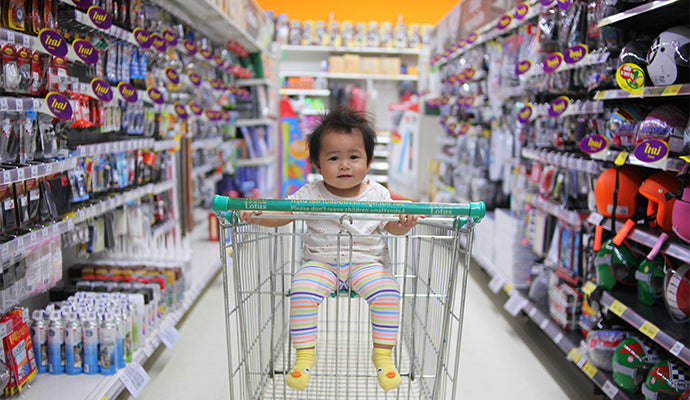 Cute little baby sitting in the front of a cart at the store, baby products are on either side of the aisle.