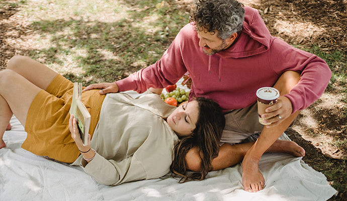 Pregnant woman lays on her partner's lap on a picnic blanket, reading a book.