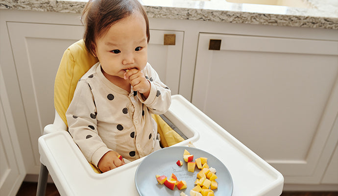 Baby sits in high chair and nibbles on chopped up pieces of apple and banana. Yum!