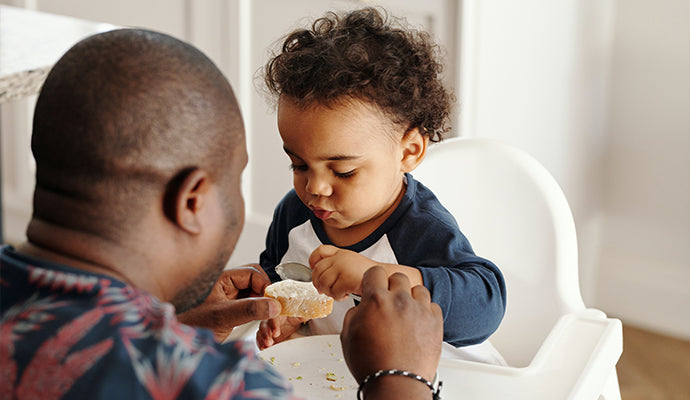 Daddy spreads butter onto a thick piece of bread for toddler in high chair to munch on.