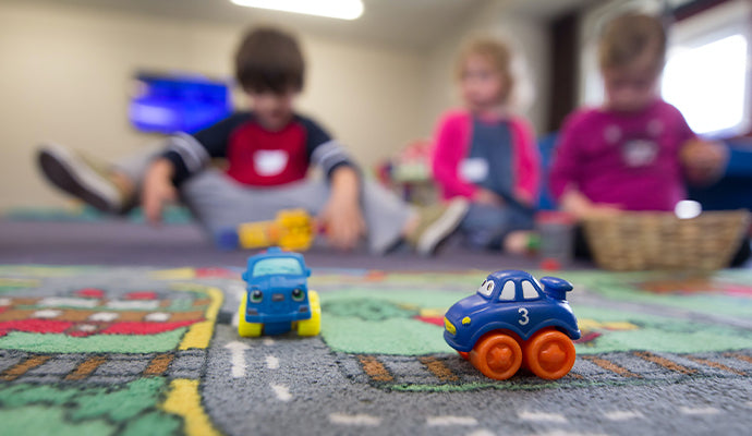 Kids use their motor skills at daycare by driving toy cars on a play rug.