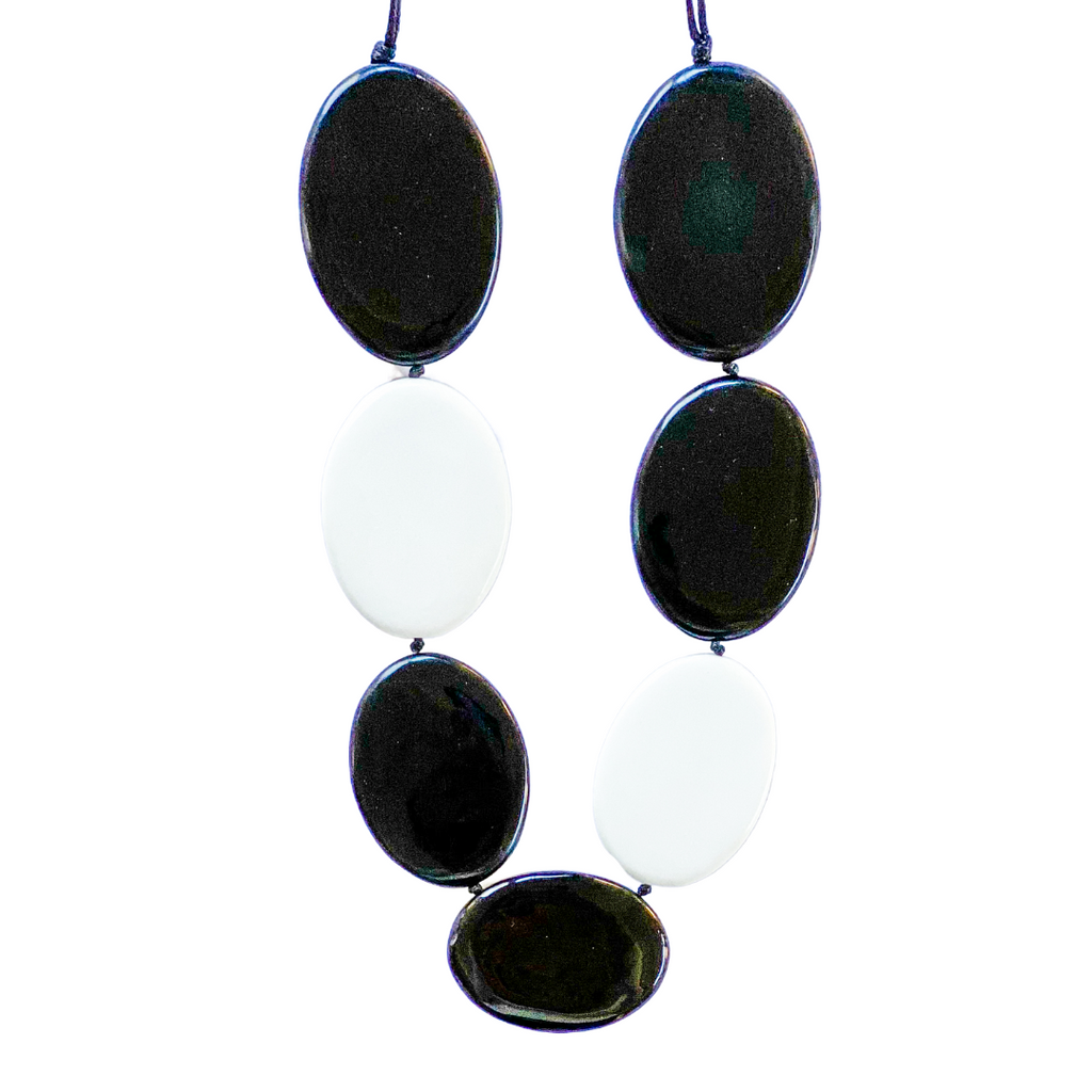 A striking black and white double sided resin necklace by Ruby Olive. Wear it black or white or a mixture of both for a completely different look.