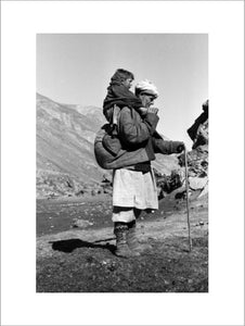 Tajik man carrying a boy on his back