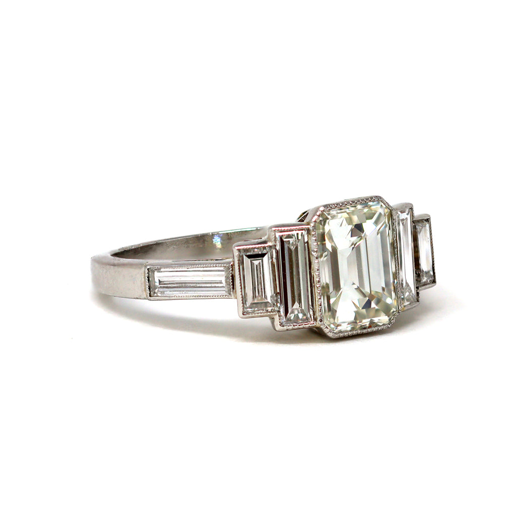 An Elegant Emerald-cut Diamond Ring with side baguettes set in Platinum angle view