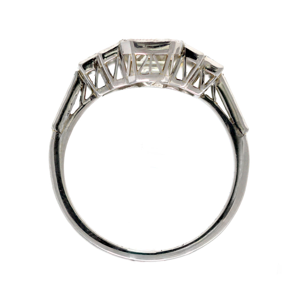 An Elegant Emerald-cut Diamond Ring with side baguettes set in Platinum front view