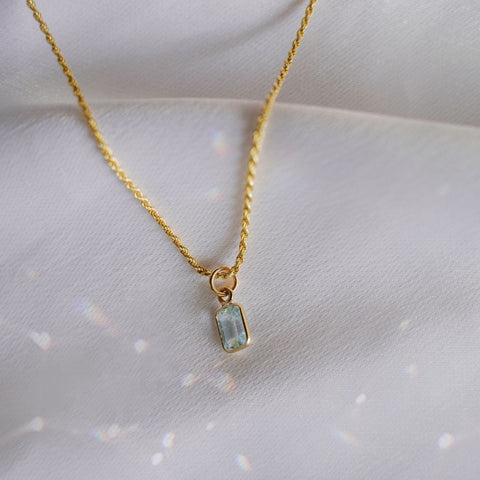 Ethically sourced gold plated necklace with semi precious blue topaz stone. Displayed on a white background.