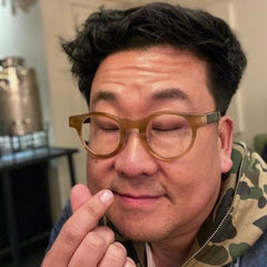 Nick Cho making a tiny heart with his fingers. Man with round glasses wearing a camo colored hoodie.