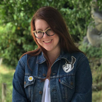 Rhian Beutler, a white woman with red hair wearing vintage style black glasses with gold accents. She is wearing a white tee shirt and denim jacket with the Oswalt character above her left pocket. Behind her are many trees and shrubbery.