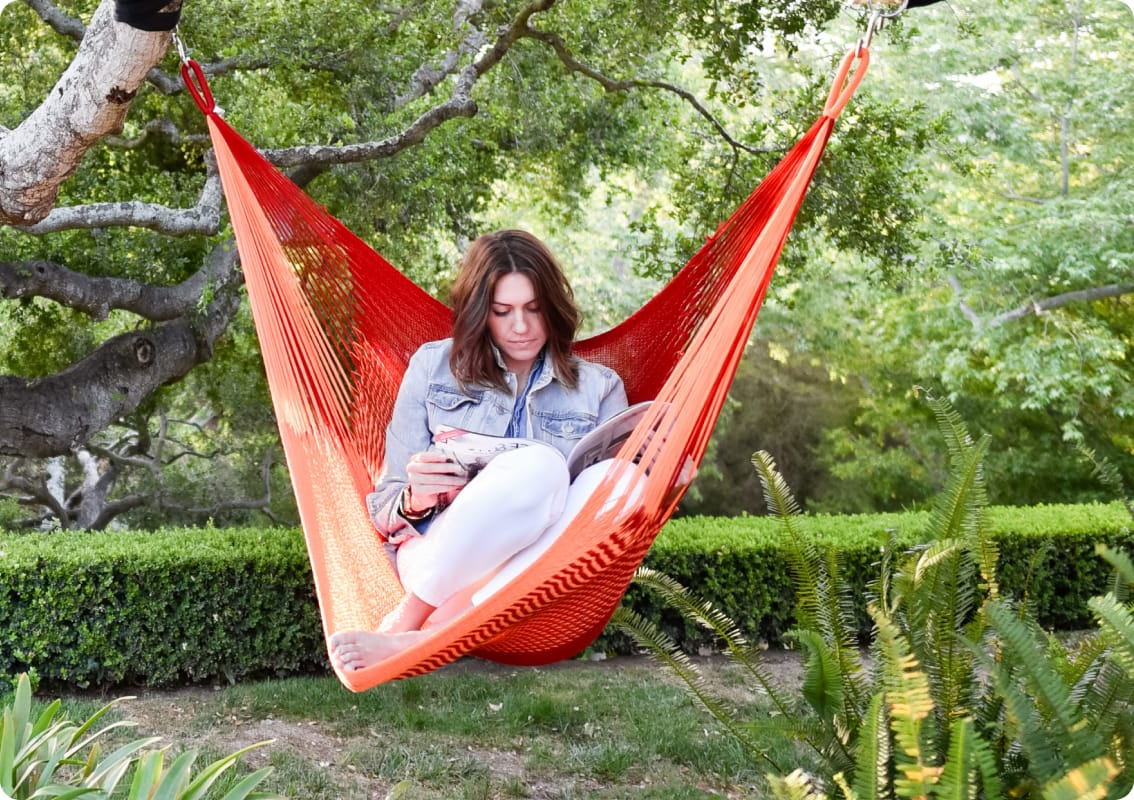 Woman sitting and reading in a red hammock
