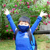 young asian boy in a long sleeve blue shirt and backpacked excitedly wearing his blue mask for school mask