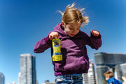 girl in purple sweatshirt jumping and looking down while holding a pouch of gnubees close banana nutritional beverage