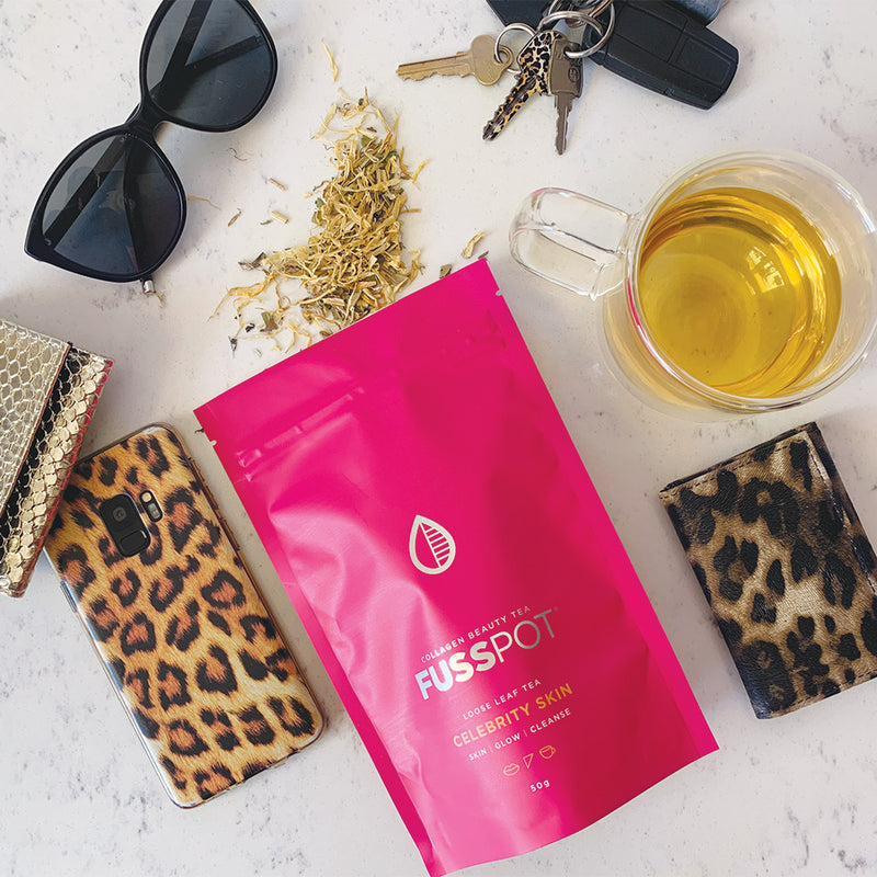 Fusspot Collagen Beauty Tea Celebrity Skin with hydrolyzed collagen peptides as a beauty tea to support skin, hair and nails, anti-ageing, reduce wrinkles.  Hot pink packaging. Beauty Product. Beauty Tea with collagen peptides,  Herbal Tea. Green Tea, Black Tea. Leopard print wallet. leopard print phone cover. designer sunglasses. teacup.
