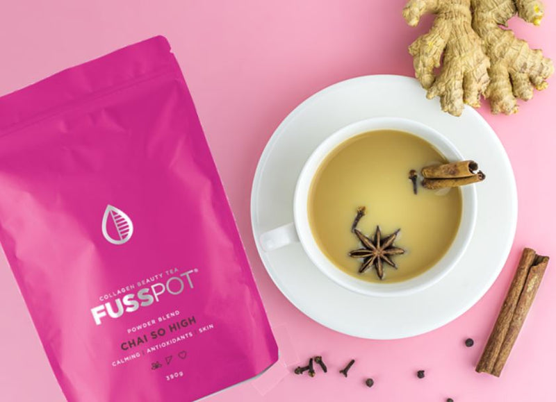 Chai with collagen. collagen chai. Fusspot Collagen Beauty Tea Celebrity Skin with hydrolyzed collagen peptides as a beauty tea to support skin, hair and nails, anti-ageing, reduce wrinkles.  Hot pink packaging. Beauty Product. Beauty Tea with collagen peptides,  chai Tea. cup of chai with cinnamon