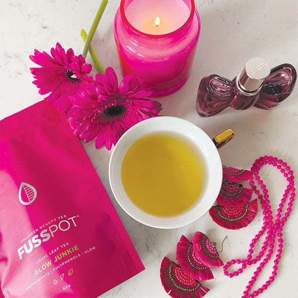 Fusspot Collagen Beauty Tea, a beauty tea with hydrolyzed collagen peptides as a beauty tea to support skin, hair and nails, anti-ageing, reduce wrinkles.  Hot pink packaging. Beauty Product. Beauty Tea with collagen peptides,  Herbal and Green Tea with pink jewelery and pink candle and pink perfume.
