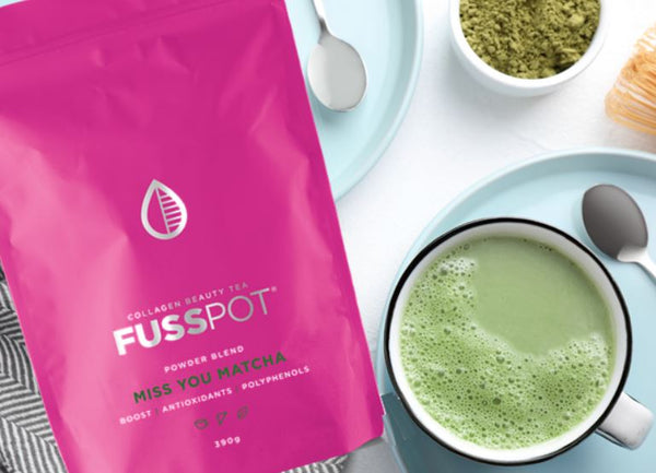 Fusspot Collagen Beauty Tea, a pure green organic matcha powder tea with hydrolyzed collagen peptides as a beauty tea to support skin, hair and nails, anti-ageing, reduce wrinkles.  Hot pink packaging. Beauty Product. Beauty Tea with collagen peptides,  green matcha in cute mug on table