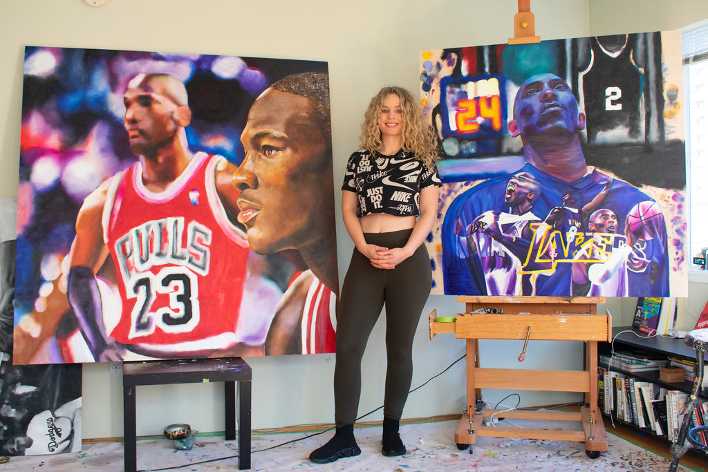 Carling Jackson standing between two paintings honoring Michael Jordan and Kobe Bryant