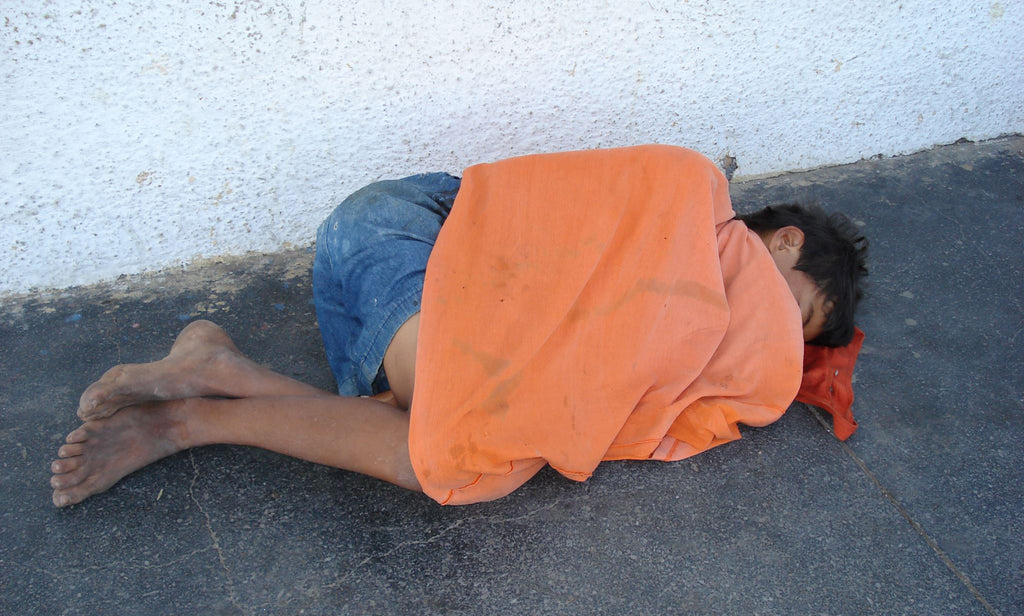 Boy sleeping on the street under a sweater.